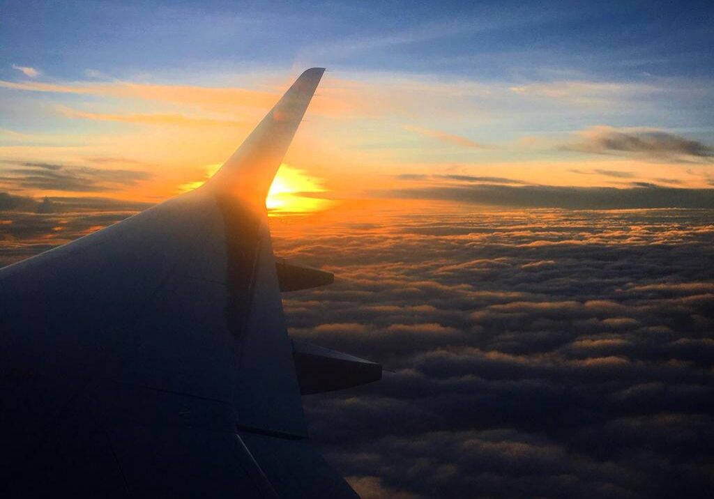 sunrise over clouds inside airplane