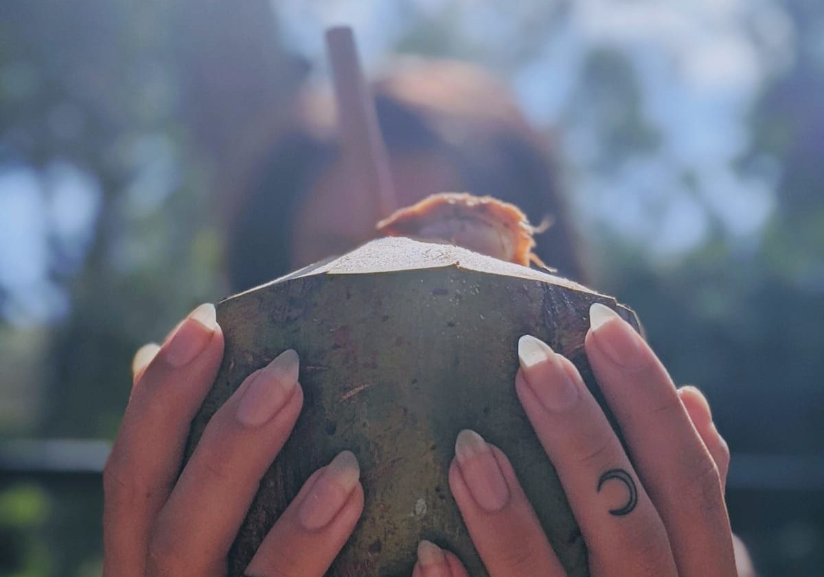 finger tattoos holding a coconut